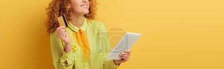 Photo pour Plan panoramique de gaie rousse femme tenant tablette numérique et carte de crédit sur jaune - image libre de droit