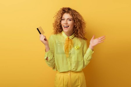 Photo for Excited redhead woman holding credit card and gesturing on yellow - Royalty Free Image