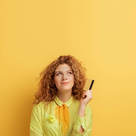 Photo for Smiling redhead woman holding credit card while thinking on yellow - Royalty Free Image