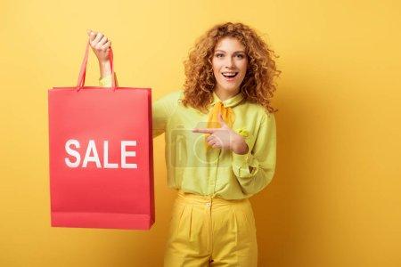 Photo pour Gaie rousse femme pointant du doigt au sac à provisions avec vente lettrage sur jaune - image libre de droit