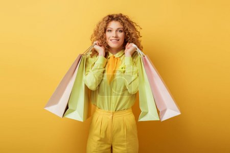 Photo for Happy redhead woman holding shopping bags on yellow - Royalty Free Image