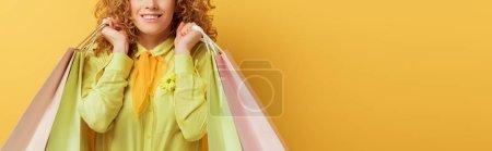 Photo pour Plan panoramique de femme rousse heureuse tenant des sacs à provisions sur jaune - image libre de droit