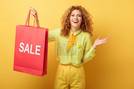 alegre pelirroja mujer sosteniendo bolsa de compras con venta de letras en amarillo