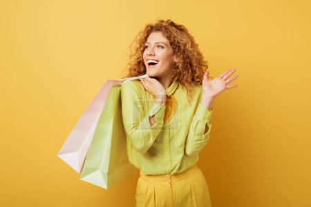 Photo pour Happy and curly woman holding shopping bags while gesturing isolated on yellow - image libre de droit