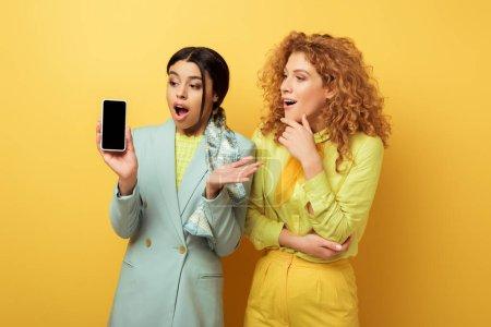 Photo pour Choqué afro-américaine fille regardant smartphone avec écran vide près surpris rousse fille sur jaune - image libre de droit