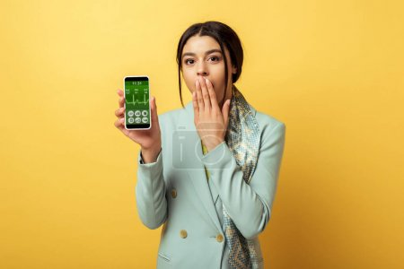 Photo for Shocked african american girl covering face and holding smartphone with medical app on yellow - Royalty Free Image