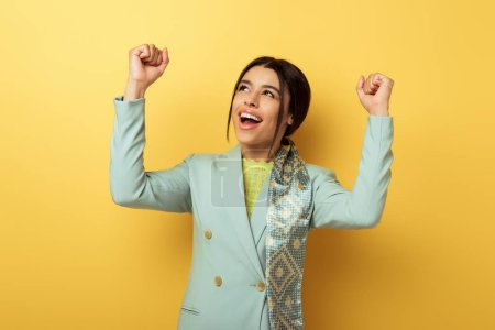 Photo for Excited african american girl with clenched fists celebrating triumph on yellow - Royalty Free Image