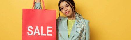 Photo pour Plan panoramique de jolie fille afro-américaine tenant sac à provisions avec lettrage de vente sur jaune - image libre de droit