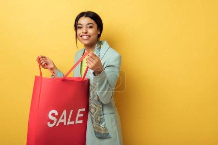 Photo pour Une Africaine d'Amérique souriante tenant un sac à provisions avec le lettrage de la vente sur jaune - image libre de droit