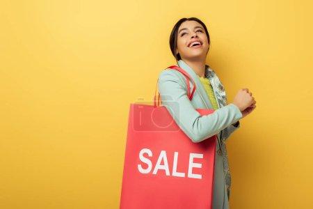 Photo pour Gai afro-américaine fille tenant sac à provisions avec vente lettrage et sourire sur jaune - image libre de droit