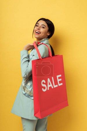 Photo pour Heureuse femme afro-américaine tenant sac à provisions avec vente lettrage et sourire sur jaune - image libre de droit