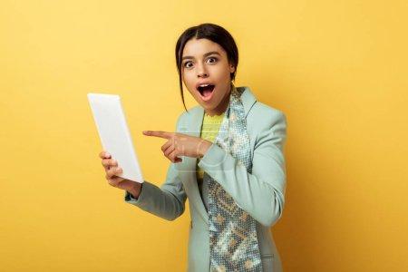 Photo pour Surpris femme afro-américaine pointant du doigt la tablette numérique sur jaune - image libre de droit