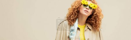 Photo for Panoramic shot of stylish redhead woman in trench coat and sunglasses with flowers posing isolated on beige - Royalty Free Image
