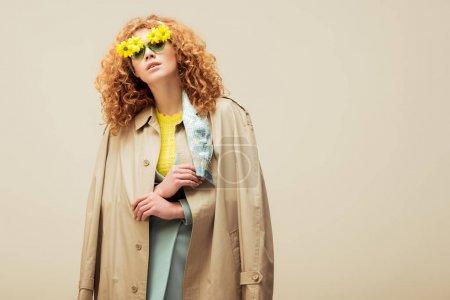 Photo pour Femme à tête rouge élégante vêtue d'un manteau de tranchée et de lunettes de soleil avec des fleurs posées isolées sur beige - image libre de droit