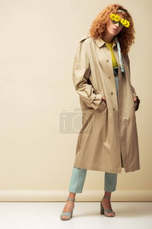Photo for Trendy redhead woman in trench coat and sunglasses with flowers standing with hands in pockets on beige - Royalty Free Image