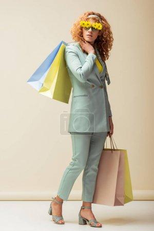 Photo pour Élégant rousse femme en costume et lunettes de soleil avec des fleurs tenant des sacs à provisions sur beige - image libre de droit
