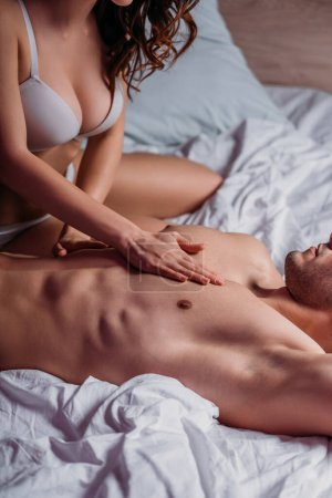 Photo pour Partial view of seductive girl with big breast in white bra making chest erotic massage to shirtless man lying on bed - image libre de droit