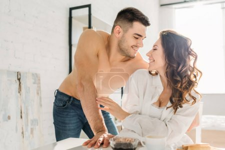 handsome shirtless man looking at happy girl sitting at kitchen table in white shirt
