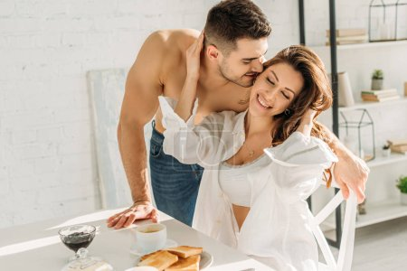 Photo pour Handsome shirtless man kissing smiling girl touching his face while sitting near breakfast - image libre de droit