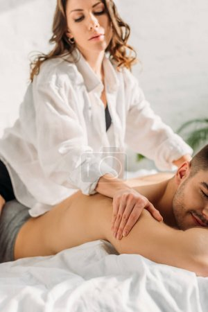 Photo pour Selective focus of attractive girl in white shirt making shoulders erotic massage to shirtless boyfriend lying on bed with closed eyes - image libre de droit