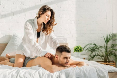 Photo pour Sexy girl in white shirt making shoulders erotic massage to shirtless boyfriend lying on bed with closed eyes - image libre de droit