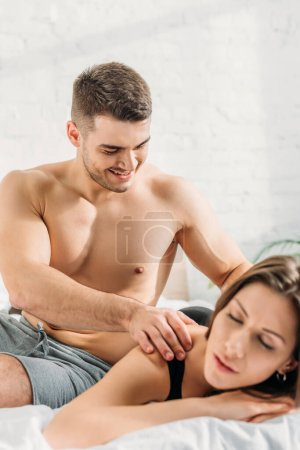 Photo for Selective focus of sexy man making shoulders erotic massage to girlfriend lying and smiling with closed eyes - Royalty Free Image