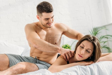 Photo for Handsome shirtless man making shoulders erotic massage to attractive girlfriend lying with closed eyes - Royalty Free Image