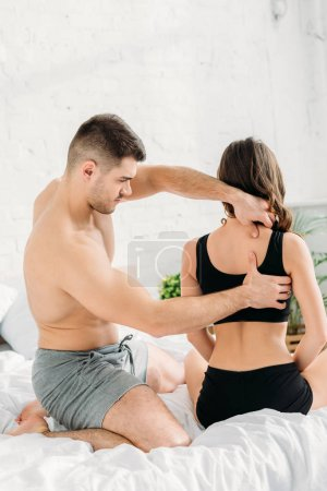 Photo for Sexy man making neck and back erotic massage to girlfriend in black top - Royalty Free Image