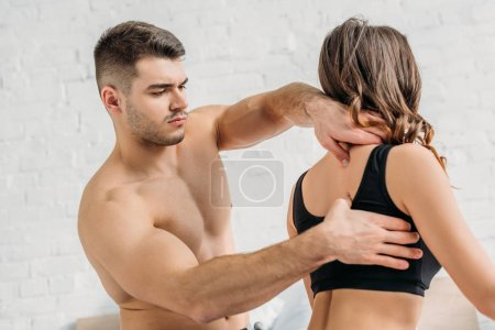 Photo for Shirtless man making neck and back erotic massage to girlfriend in black top - Royalty Free Image