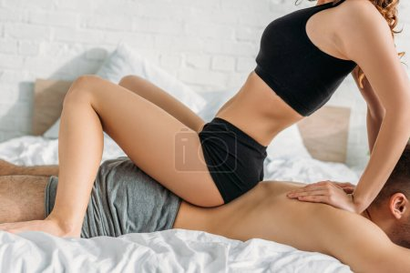 Photo pour Cropped view of girl in black underwear making erotic massage to man while sitting on his loin - image libre de droit