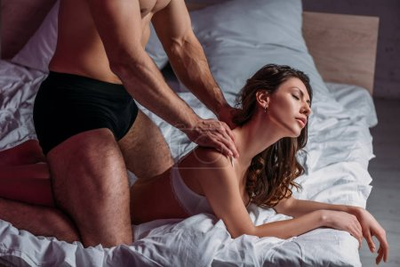 Photo for Partial view of shirtless man making shoulders erotic massage to sexy girlfriend lying on bed with closed eyes - Royalty Free Image