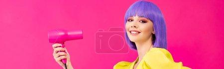 Photo pour Plan panoramique de joyeuse fille pop art en perruque violette à l'aide d'un sèche-cheveux, isolé sur rose - image libre de droit