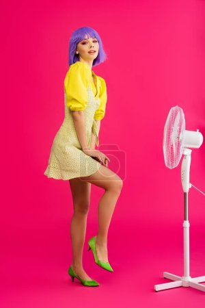 Photo pour Jolie fille pop art en perruque violette debout près ventilateur électrique, sur rose - image libre de droit