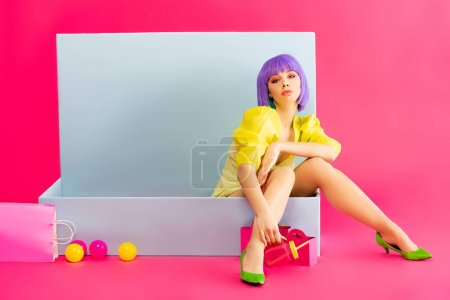 Photo for Bored girl in purple wig as doll sitting in blue box with balls and shopping bags, on pink - Royalty Free Image