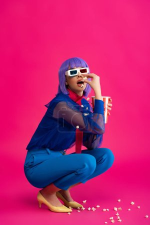 beautiful pop art girl in purple wig and 3d glasses eating popcorn, on pink