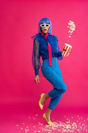 Photo pour Surprised pop art girl in purple wig and 3d glasses throwing popcorn, on pink - image libre de droit