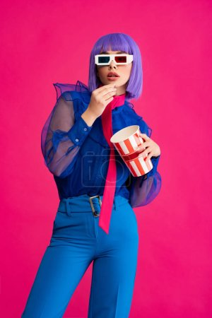 pop art girl in purple wig and 3d glasses eating popcorn, isolated on pink