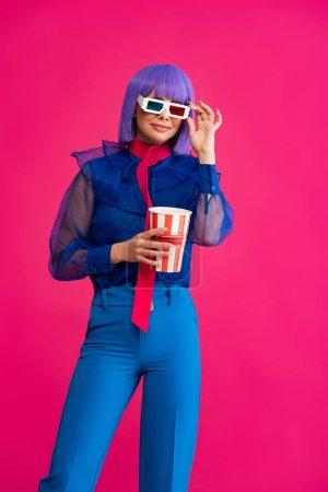 Photo pour Heureuse fille pop art en perruque violette et lunettes 3d tenant pop-corn, isolé sur rose - image libre de droit