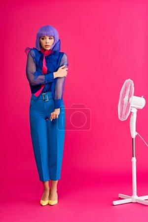 Photo pour Froide fille élégante en perruque violette debout près ventilateur électrique, sur rose - image libre de droit