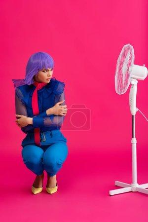 Photo pour Triste fille froide en perruque violette debout près ventilateur électrique, sur rose - image libre de droit