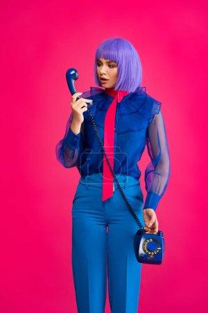 Photo pour Fille à la mode en perruque pourpre parler sur le téléphone rétro, isolé sur rose - image libre de droit