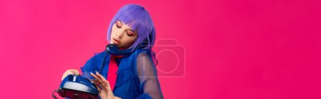 Photo for Panoramic shot of beautiful trendy girl in purple wig talking on retro phone, isolated on pink - Royalty Free Image