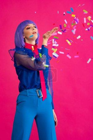 Photo pour Attrayant pop art fille en violet perruque soufflant confettis, isolé sur rose - image libre de droit