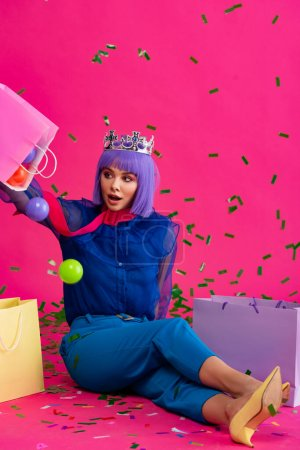 Photo for Shocked woman in purple wig and crown sitting with shopping bags, balls and holiday confetti, on pink - Royalty Free Image