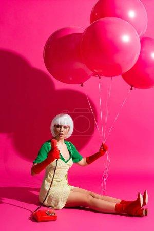 Photo pour Choqué fille pop art en perruque blanche avec des ballons regardant téléphone vintage, sur rose - image libre de droit
