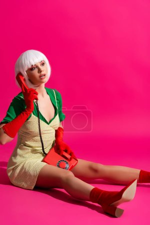 Photo for Attractive pop art girl in white wig talking on vintage phone, on pink - Royalty Free Image