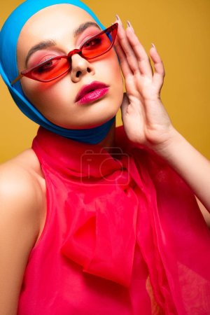 Photo for Seductive fashionable girl in trendy scarf and red sunglasses, isolated on yellow - Royalty Free Image
