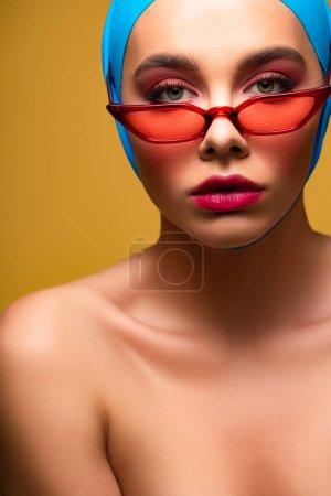 Photo pour Sexy fille nue à la mode en écharpe à la mode et lunettes de soleil rouges, isolé sur jaune - image libre de droit
