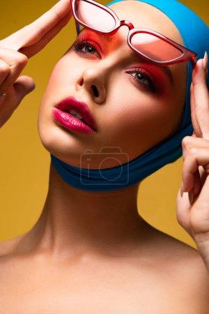 Photo pour Beau modèle à la mode en foulard à la mode et lunettes de soleil rouges, isolé sur jaune - image libre de droit