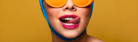 Photo for Panoramic shot of girl in scarf and fashionable sunglasses licking lip, isolated on yellow - Royalty Free Image